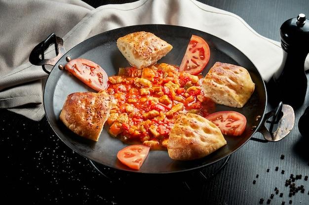 Турецкий куриный гуляш в красном соусе с болгарским перцем и традиционными булочками в металлической посуде на черном столе. крупным планом, выборочный фокус