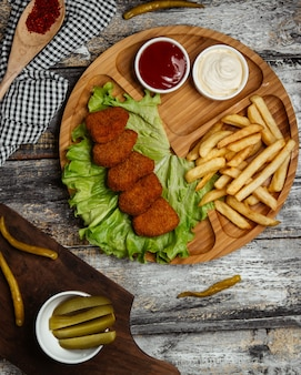 Turkish chig kogte in lettuce iwht french fries and sauces.