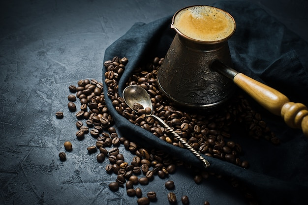 Turkish coffee in a cezve, the breakfast. black background, top view, close up