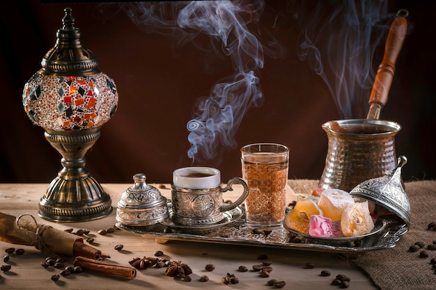 Turkish coffee in cezve and traditional turkish delight. steam over a cup. antique lamp