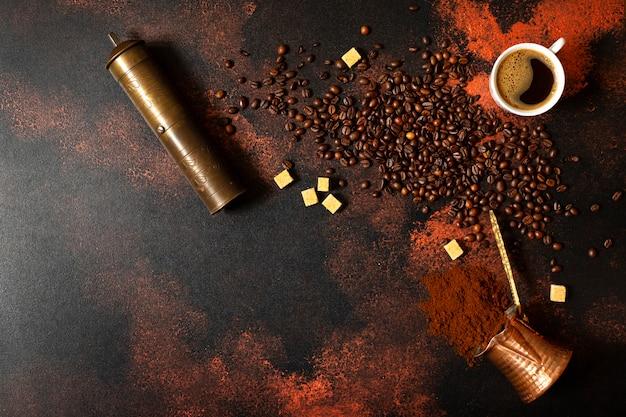 トルココーヒーのコンセプトです。銅のコーヒーポット(cezve)、ビンテージコーヒーグラインダー、カップ、コーヒー豆、暗いビンテージ背景に砂糖。テキストのためのスペース。上面図