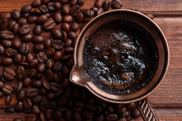 Турецкий кофе в турке на деревянном столе крупным планом с кофейными зернами вид сверху выборочный фокус