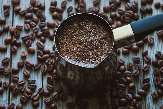 Турецкий кофе в кофейнике, кофейные зерна, разбросанные на деревянном столе