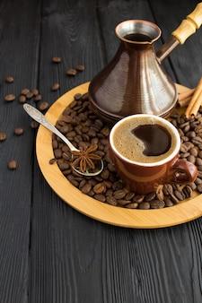 Турецкий кофе в коричневой чашке и турок на разделочной доске на черной деревянной поверхности. копировать пространство вертикальное расположение.