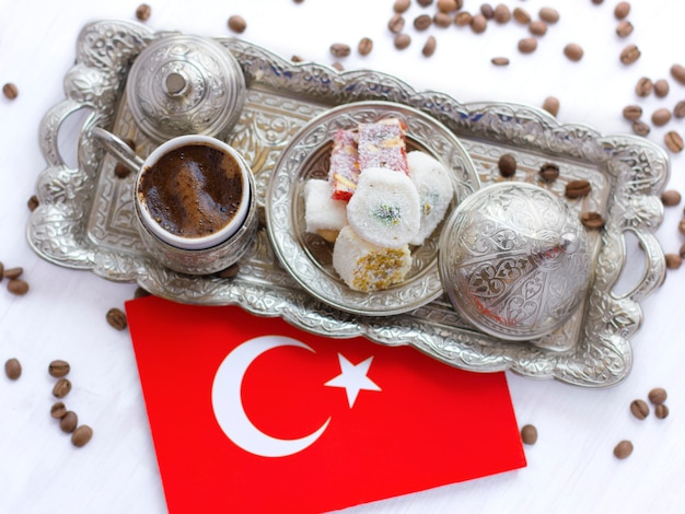Turkish coffee on a traditional silver tray with turkish sweets and the red flag of turkey