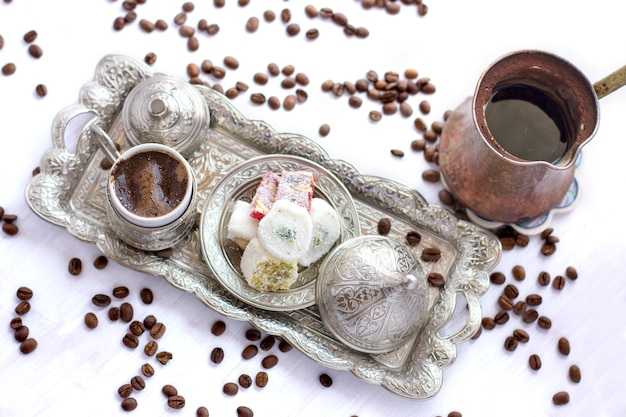 Turkish coffee with traditional turkish sweets in silver mug and jezve