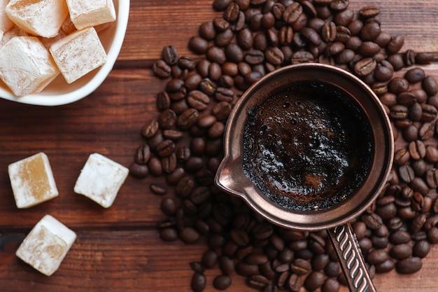 커피 콩과 함께 나무 테이블 근접 촬영에 cezve에서 터키 기쁨과 터키 커피