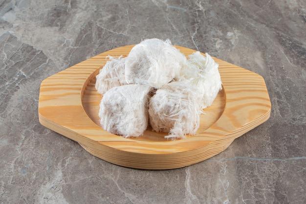 Турецкая сахарная вата в деревянной тарелке на синем.