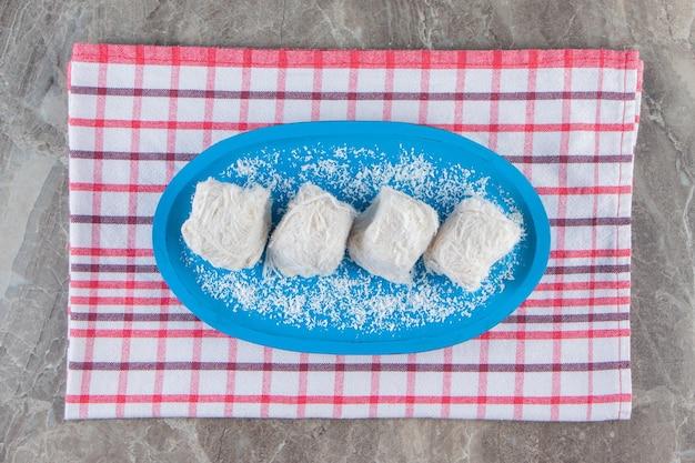 Турецкая сахарная вата в деревянной тарелке на кухонном полотенце на синем.