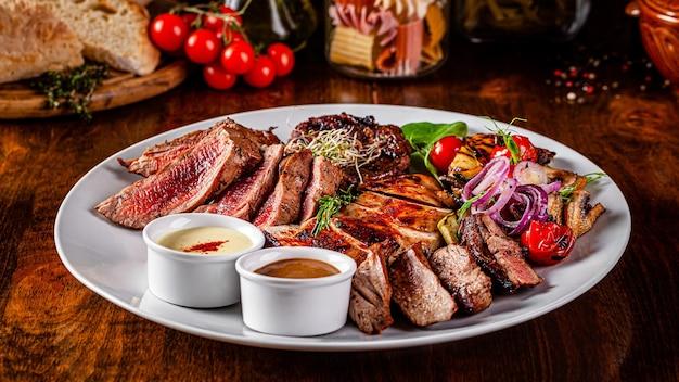 Турецкая кухня. мясное ассорти на гриле, баранина, курица, свинина с овощами гриль. обслуживание блюд в ресторане на белой тарелке