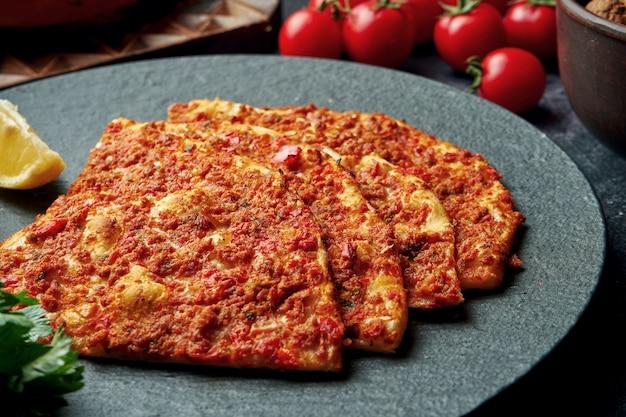 Блюдо турецкой кухни - пиде с фаршем и помидорами на черной тарелке. турецкий лахмаджун, крупный план,