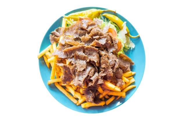 Турецкая кухня. мясо донер-кебаб с картофелем фри pommes и салатом на тарелке, изолированной на белом фоне.