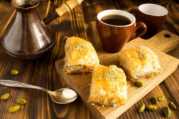 茶色の木製の背景のまな板にロクムとコーヒー