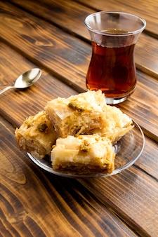Рахат-лукум и чай на деревянных фоне
