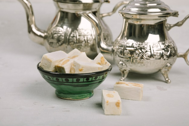Turkish delight in bowl with teapots on table