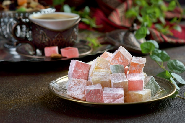 Turkish delight on a dark background with a cup of coffee