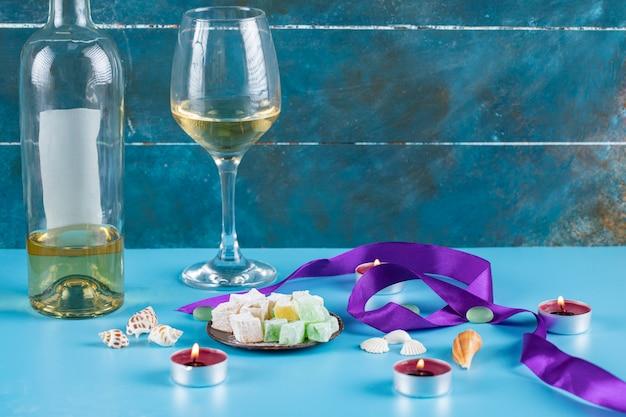 Лукум лукум в металлическом блюдце с бокалом вина