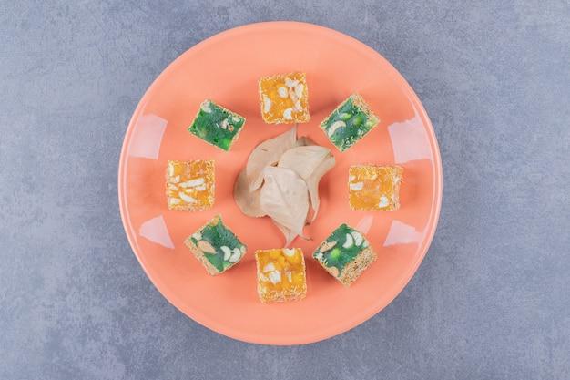 Турецкие сладости. лукум или рахат лукум на оранжевой тарелке.