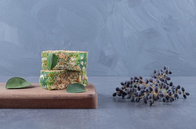 Турецкие сладости. лукум или рахат лукум с фундуком на деревянной доске на сером фоне.