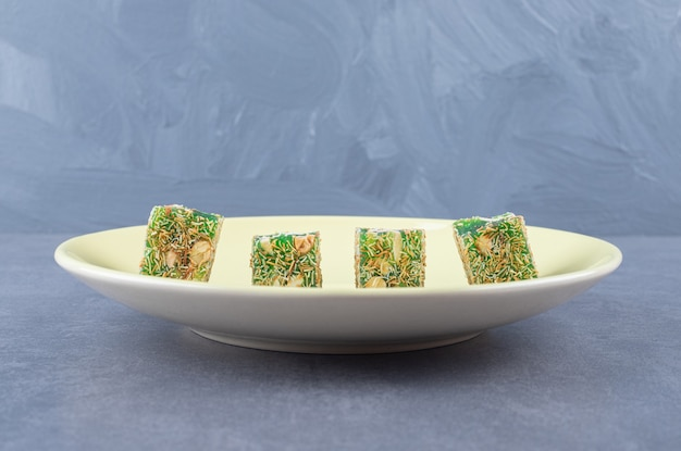 Турецкие сладости. лукум или рахат лукум с лесными орехами на желтом небе.