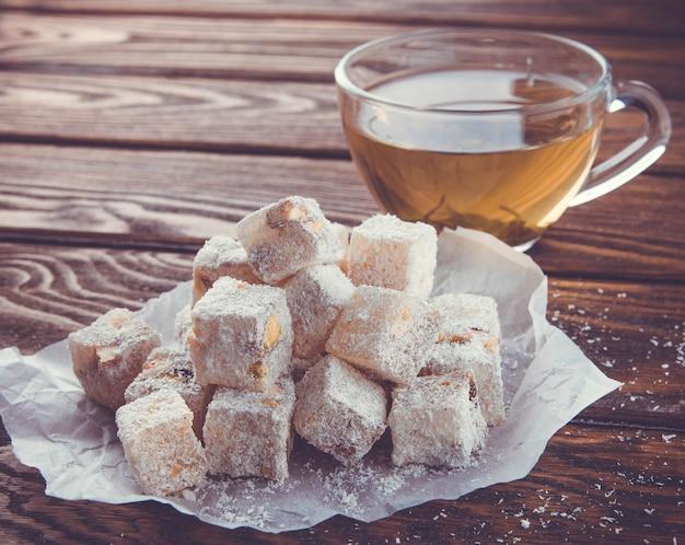 木製の背景にお茶とトルコ菓子ロクム
