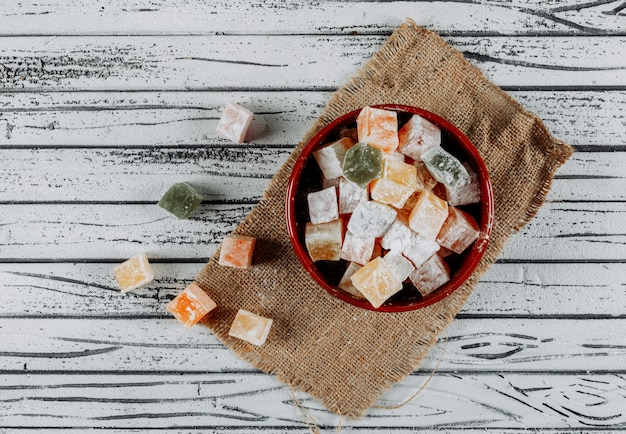 Turkish delight lokums in a bowl on a cloth and white wooden background. top view.