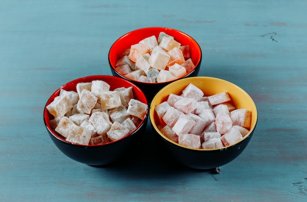 Turkish delight lokums in a bowls on a cyan blue wooden background. high angle view.