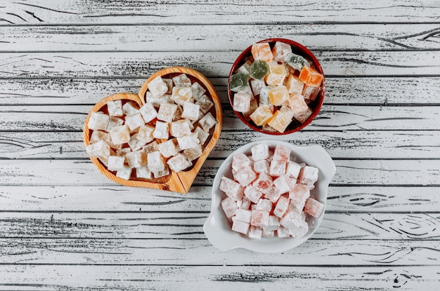 Turkish delight lokums in a bowls on a white wooden background. top view.