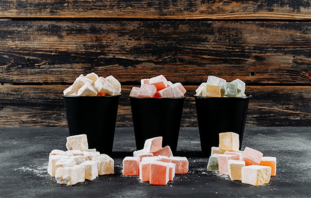 Turkish delight lokums in a buckets side view on a black textured background space for text