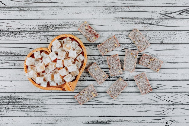 Turkish delight lokums in a heart shaped wooden bowl top view on a white wooden background
