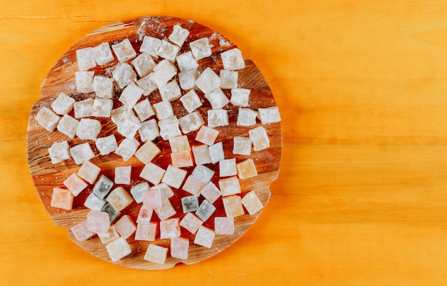 Turkish delight lokums in a wood on a yellow wooden background. flat lay. space for text