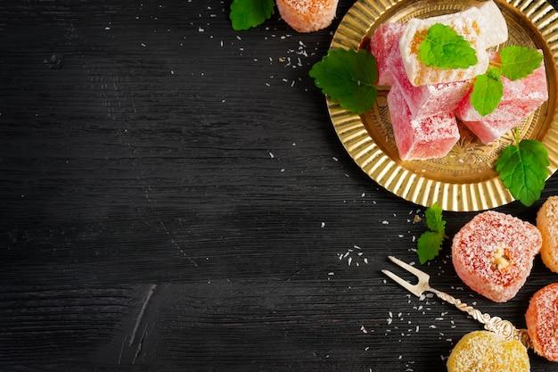 Turkish delight on oriental metal plate on black table
