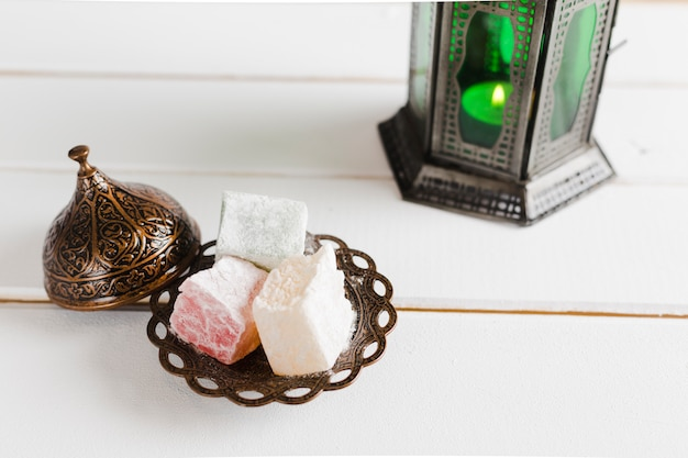 Turkish delight on plate with lid and candlestick
