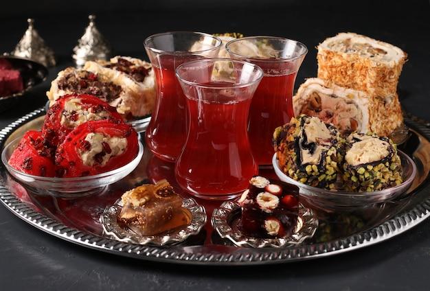 Turkish delight and pomegranate tea on metal tray on dark surface, closeup, horizontal format