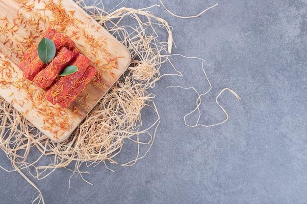 Рахат лукум рахат лукум на деревянной доске с декоративной соломой.