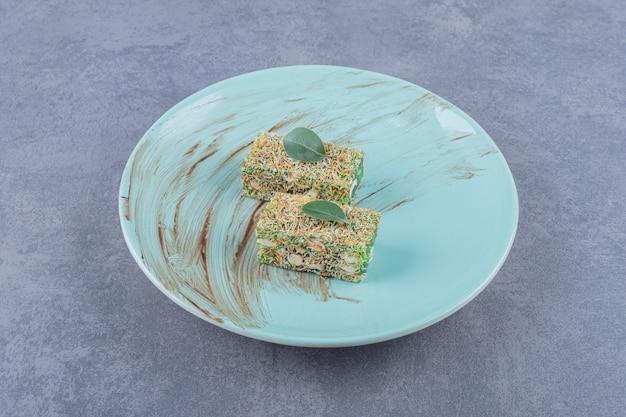 Turkish delight rahat lokum with hazelnuts on green plate.