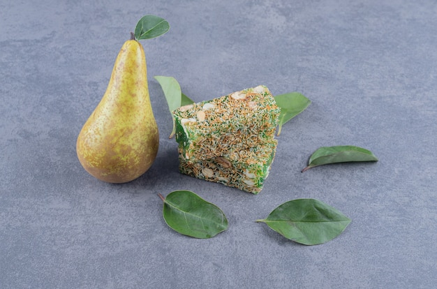 Turkish delight rahat lokum with hazelnuts and pear on grey background.