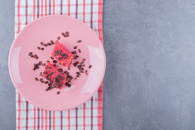 Turkish delight rahat lokum with pistachios and dry raisins on pink plate