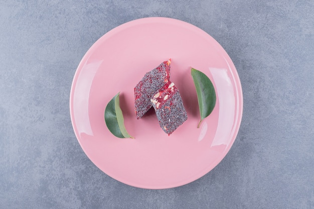 Turkish delight rahat lokum with pistachios on pink plate.
