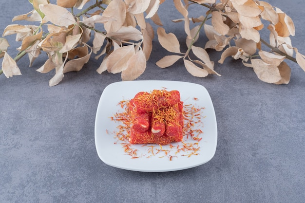 Turkish delight rahat lokum with pistachios on white plate.