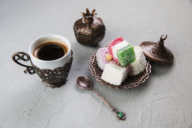 Turkish delight with coffee cup on grey table