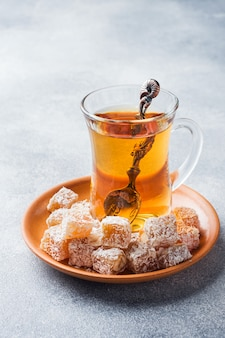 Turkish delight with hazelnut in carved metal bowl and tea in glass cup