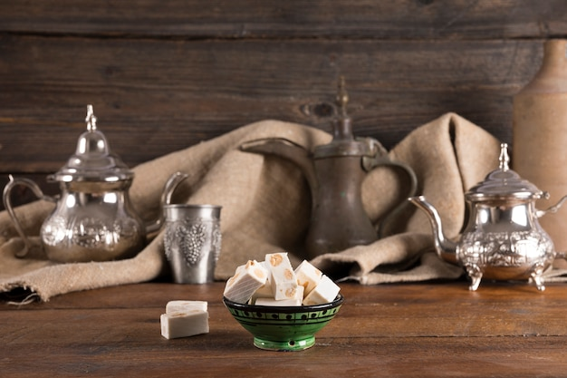 Turkish delight with teapots on wooden table