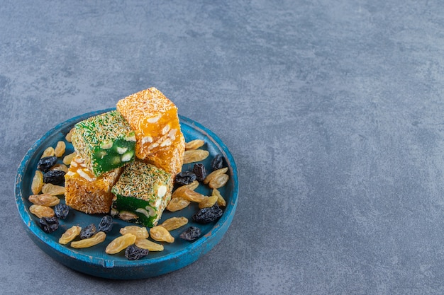 대리석 배경에 나무 접시에 터키식 기쁨과 건포도.