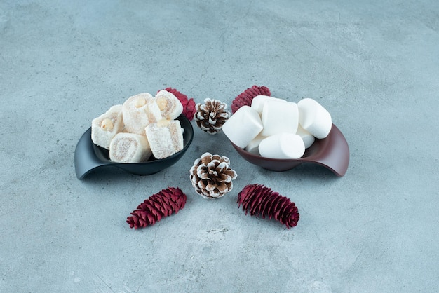 Turkish delights and marshmallows in small bowls next to pine cones on marble.