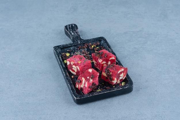 Delizie turche e uvetta sul tagliere, sul tavolo di marmo.
