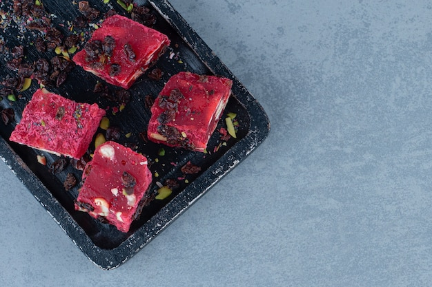 Turkish delights and raisins on the cutting board , on marble table.