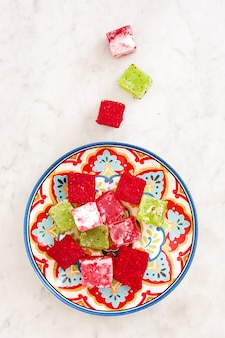 Turkish delights in traditional plate on white marble