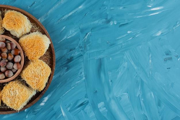Рахат-лукум с орехами макадамия на темной деревянной тарелке