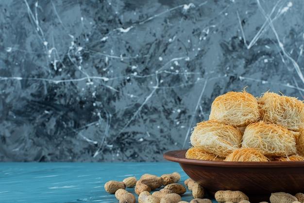 Delizie turche con noci di arachidi su un piatto di legno scuro.